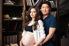 Беременная молодая женщина и человек стоят бортовая - мимо - сторона Беременность Стоковое Изображение RF