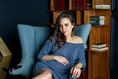 Беременная молодая женщина сидя в стуле стоковое фото