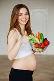 Беременная молодая женщина варя овощи Здоровая еда - Vegetable салат Диета вокруг номеров измерения дисплея принципиальной схемы  Стоковое фото RF