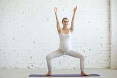 Беременная молодая женщина делая пренатальную йогу Представление сидения на корточках Sumo стоковое фото rf