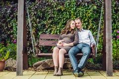 Беременная молодая женщина и ее супруг Счастливая семья сидя на качании, держа живот женщина парка супоросая ослабляя Стоковое Фото