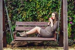 Беременная молодая женщина сидя на качании, с чашкой чаю женщина парка супоросая ослабляя Стоковое Фото