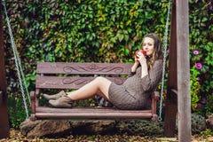 Беременная молодая женщина сидя на качании, с чашкой чаю женщина парка супоросая ослабляя Стоковые Фото