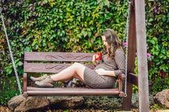 Беременная молодая женщина сидя на качании, с чашкой чаю женщина парка супоросая ослабляя Стоковые Изображения