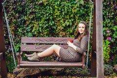 Беременная молодая женщина сидя на качании, с чашкой чаю женщина парка супоросая ослабляя Стоковые Фотографии RF