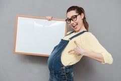 Беременная счастливая дама держа доску и указывать copyspace Стоковая Фотография