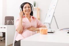 Беременная усмехаясь женщина отдыхая в офисе Стоковая Фотография