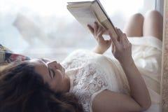 Беременное чтение девушки Стоковые Изображения RF