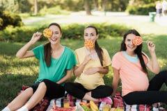 3 беременной женщины представляя в пикнике паркуют с большими покрашенными конфетами Стоковое Фото