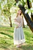 Беременность, люди и концепция материнства - счастливая беременная азиатская женщина идя на парк стоковая фотография rf