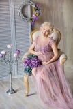 Беременность, материнство и счастливая будущая концепция матери - беременная женщина в воздушном фиолетовом платье с цветками бук стоковые изображения rf