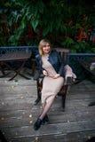 Беременность, материнство и счастье Стильная молодая беременная женщина имея остатки в парке, сидя на деревянном armcheir красиве стоковое фото