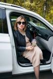 Беременность, материнство и счастье Стильная молодая беременная женщина имея остатки ее автомобиль, сидя в белом автомобиле краси стоковые фото