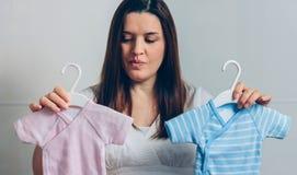 Беременные выбирая bodysuits младенца стоковая фотография rf