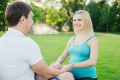Беременные женщины делая йогу с ее человеком внешним Стоковая Фотография