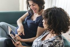 Беременные женщины используя цифровую таблетку совместно Стоковые Фото