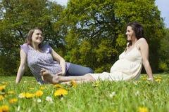 Беременные женщины сидя на траве Стоковые Изображения