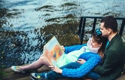 Беременные женщины с супругом около озера Стоковые Изображения
