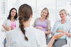 Беременные женщины слушая к показывать доктор на антнатальном классе Стоковая Фотография