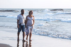 Беременные пары идя на пляж Стоковые Фото