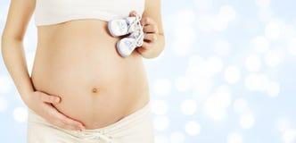 Беременный живот держа добычи младенца новорожденного, Newborn одежду Стоковые Фотографии RF
