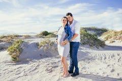 Беременный молодой взаимодействовать пар, стоя outdoors, сцена пляжа Стоковое фото RF