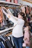 Беременный ребенок матери и девушки выбирая одежды Стоковое Изображение RF