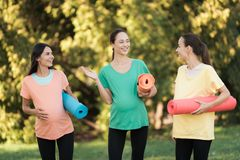 3 беременных девушки представляя в парке с циновками йоги в руке Они усмехаются и имеются потеху Стоковая Фотография