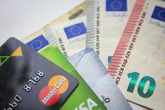 Берлин, Германия - 29-ое августа 2017: Пластичная кредитная карточка Mastercard и виза на предпосылке банкнот евро отражение дег  Стоковое фото RF