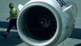 БЕРЛИН, ГЕРМАНИЯ - 18-ОЕ МАЯ 2017 Двигатель самолета авиакомпании SAS работая и идя техник авиапорта Стоковые Изображения