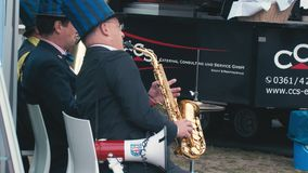 БЕРЛИН, ГЕРМАНИЯ - 2-ОЕ ОКТЯБРЯ 2018 Музыканты улицы замедленного движения играют аппаратуры ветра и банджо Пиво напитка на акции видеоматериалы