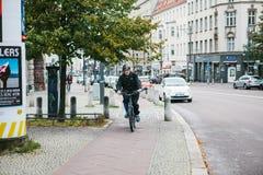 Берлин, 12-ое декабря 2017: Пожилой человек на самокате едет специальный путь велосипеда вдоль улицы города рядом с Стоковое Фото