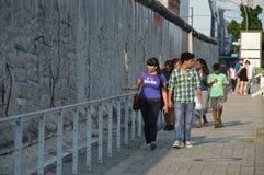 Берлин, Германия - июль 2015 - туристы идя рядом с Берлинской стеной Стоковые Фото