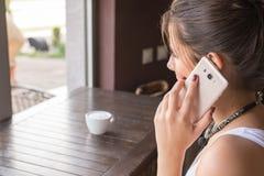 Беседа девушки к сотовому телефону в кофейне Взгляд за плечом девушки Стоковая Фотография