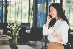 Беседа коммерсантки на умном телефоне на рабочем месте startup женщина wo Стоковые Изображения RF