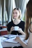 Беседа молодой дамы 2 сидит на таблице в кафе Стоковое Изображение RF
