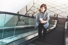 Беседа работницы через умный телефон пока эскалатор Стоковая Фотография