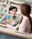 Беседа 2 девушок сидя на таблице Стоковое Изображение