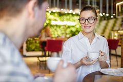 Беседуя женщина и человек имея кофе стоковое фото rf