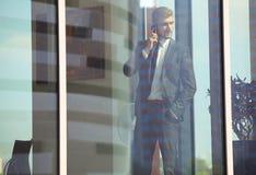 Беседа бизнесмена к мобильному телефону и взгляд из окна Стоковые Изображения