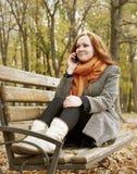 Беседа девушки Redhead на телефоне и сидеть на стенде в парке города, сезоне падения Стоковые Изображения