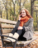Беседа девушки Redhead на телефоне и сидеть на стенде в парке города, сезоне падения Стоковая Фотография