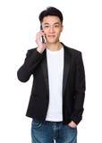 Беседа молодого человека к мобильному телефону стоковое фото