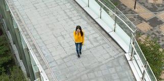 Беседа молодой женщины к мобильному телефону Стоковое Изображение
