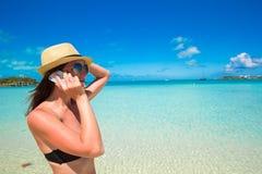 Беседа молодой женщины на ее телефоне на тропическом пляже стоковое фото rf