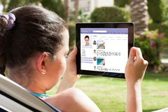 Беседовать молодой женщины онлайн Стоковое Изображение
