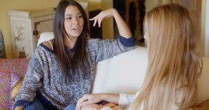 Беседовать 2 молодых женщин ослабляя дома Стоковые Изображения RF