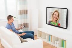 Беседовать человека видео- используя телевидение Стоковая Фотография