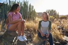 Беседуя подруги сидя на утесах Стоковая Фотография RF