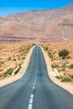 Бесконечная дорога в пустыне Сахары с голубым небом, марокканськой Африкой Стоковые Изображения